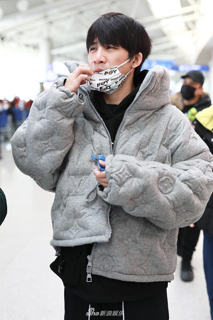 吃货属性曝光!大张伟机场一路吃零食 白色印花口罩太个性
